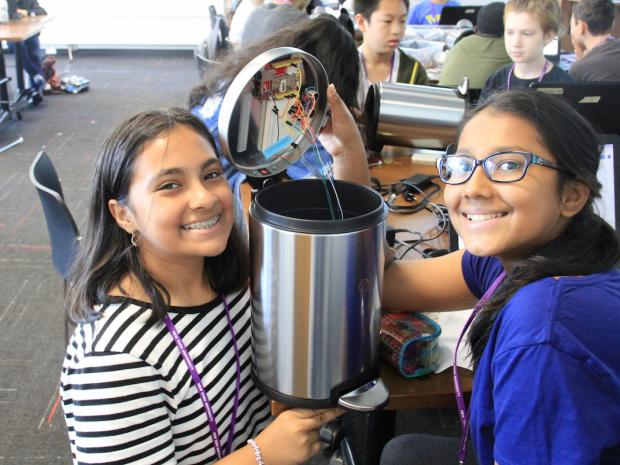 2 young girls working on a robotics project