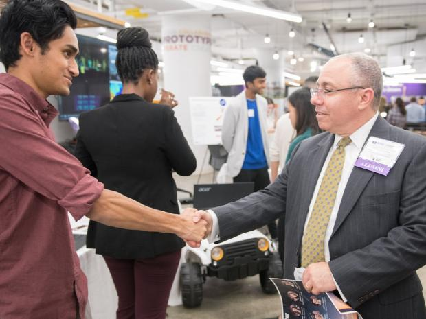 student shaking hand with an alum